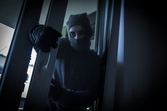 Burglar Breaking Into House By Forcing Door With Crowbar