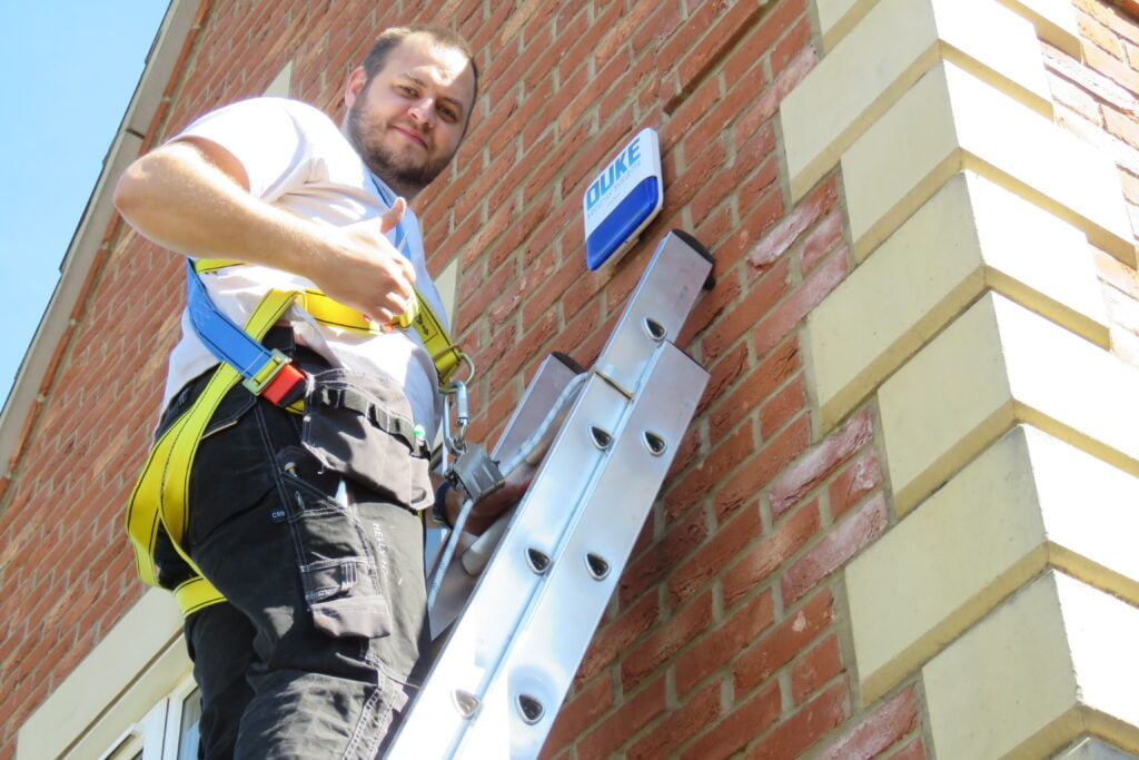 Man on a latter with thumps up after installing intruder / Burglar home security system